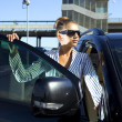 Woman in black sunglasses near car - Stock Photo