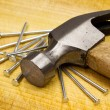 Stock Photo: Hammer and nails on wooden board