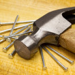 Hammer and nails on wooden board — Stock Photo #3843015