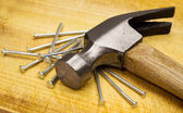 Hammer and nails on wooden board — Stock Photo