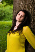 Beautiful woman standing by the tree — Stock Photo
