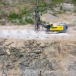 Drilling machine in open cast mining quarry — Stock Photo