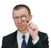 Businessman with a magnifying glass — Stock Photo