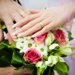 Hands of newly married with wedding bouq — Stock Photo