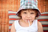 Child drinking juice through a straw — Stock Photo