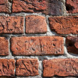 Inscriptions chiseled in bricks wall — Stock Photo