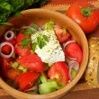 Royalty-Free Stock Photo: Greek salad on a striped tablecloth