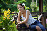 The girl sits on a shop in a garden. — Stockfoto