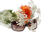 Sun glasses and bunch of flowers — Stock Photo