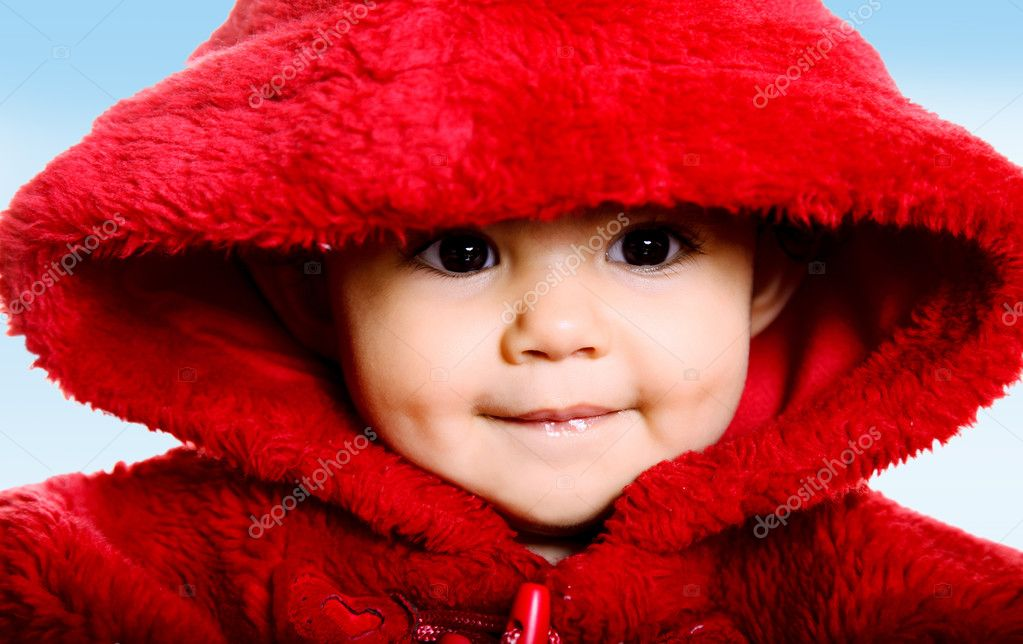 Beauty baby looking at the camera with red hood over sky background — Photo #3137201