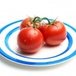 Three tomatoes with water drops on plate — Stock Photo