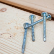 Four screws on wood plank — Stock Photo