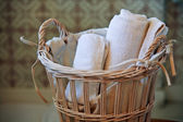 Two white rolled towels in wicker basket — Stok fotoğraf