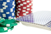 Three color poker chip stacks and cards deck — Stock Photo