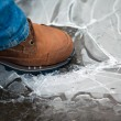 Stock Photo: Men leg in shoe crushing thin ice