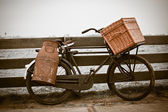 Old bicycle with can and basket — Stock Photo