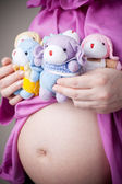 Teddy bears sitting on pregnant belly — Stock Photo