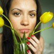 Stock Photo: Young woman with bouquet of tulips