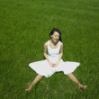 Cheerful young woman on a green field - Stock Photo