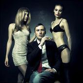 Pohledný muž a dvě ženy — Stock fotografie