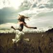 Girl running across field - Stockfoto