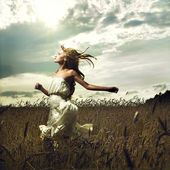 Girl running across field — Stockfoto
