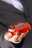 Businessman handing over a red sport car — Stock Photo