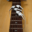 Earbuds as Fingers on Guitar - Stock Photo