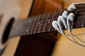 Earbuds as Fingers on Guitar — Stock Photo