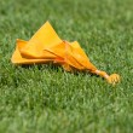 Постер, плакат: Yellow Penalty Flag on Green Grass