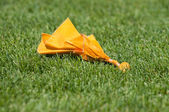 Yellow Penalty Flag on Green Grass — Stock Photo