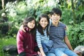 Three children sitting outdoors — Stock Photo