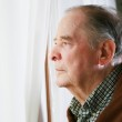 Elderly man looking out window — Stock Photo