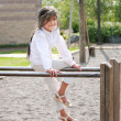 Little girl sitting on top of bars — Stock Photo #3121550