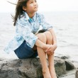Stock Photo: Nine year old girl sitting by lake