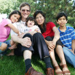 Large multiracial family sitting on lawn — Stock Photo #3121845