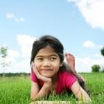 Little girl lying on grass in summer — Stock Photo #3122002