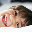 Stock Photo: Happy little toddler boy lying down