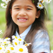 Beautiful little girl with daisies — Stock Photo