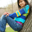 Adorable little girl sitting in tree — Stock Photo