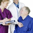 Doctor examining elderly patient — Stock Photo