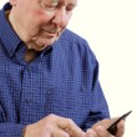 Elderly man dialing cell phone — Stock Photo
