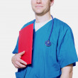 Handsome doctor holding folder — Stock Photo