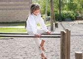 Little girl sitting on top of bars — Stock Photo