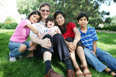 Large multiracial family sitting on lawn — Stockfoto