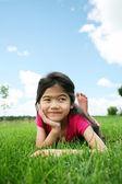 Petite fille couché sur l'herbe en été — Photo
