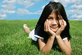 Little girl lying on grass in summer — Zdjęcie stockowe