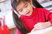Happy six year old girl drawing. — Stock Photo