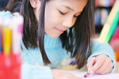 Happy nine year old girl drawing. — Stock Photo