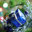 Blue present ornament nestled in CHristmas tree. — Stock Photo